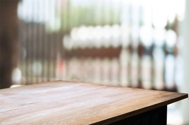 empty wooden desk over blurred interior decoration background stock photo