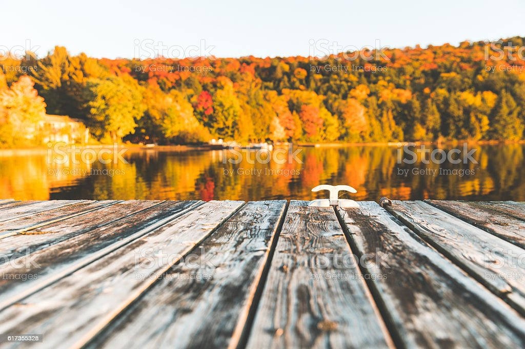 Empty wooden dock on the lake with trees on background stock photo
