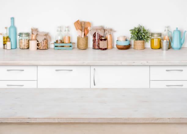 leere holz küchentisch auf unscharfen hintergrund von lebensmittelzutaten - küche deko grün stock-fotos und bilder
