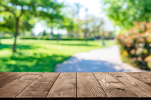 Empty rustic wooden table with defocused park footpath and green lush foliage at background. Ideal for product display on top of the table. Predominant color are green and brown. XXXL 63Mp outdoors photo taken with SONY A7rII and Zeiss Batis 40mm F2.0 CF