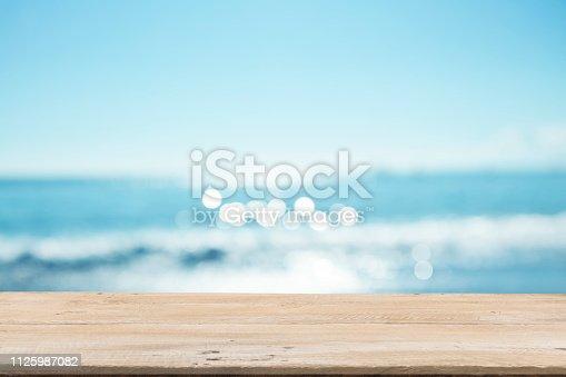 1125987088istockphoto Empty Wooden Planks with Blur Beach on Background 1125987082