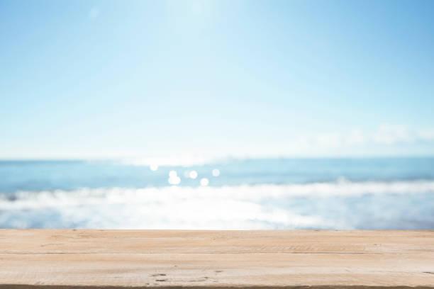 tablones de madera vacíos con playa de desenfoque en el fondo - playa fotografías e imágenes de stock