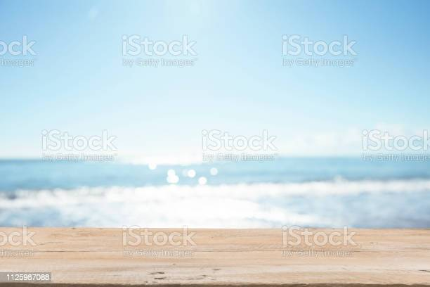 Photo of Empty Wooden Planks with Blur Beach on Background