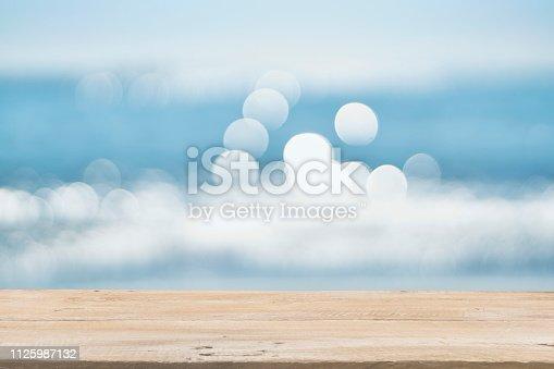 1125987088istockphoto Empty Wooden Planks with Blur Beach on Background 1125987132