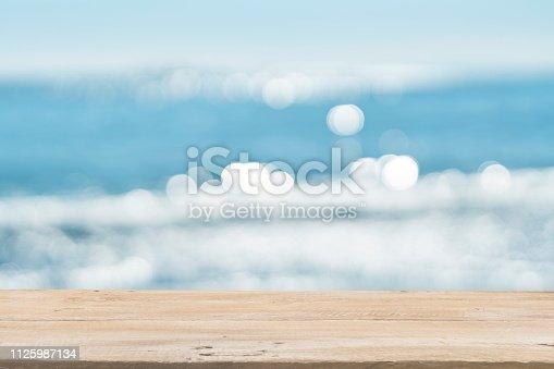 1125987088istockphoto Empty Wooden Planks with Blur Beach on Background 1125987134
