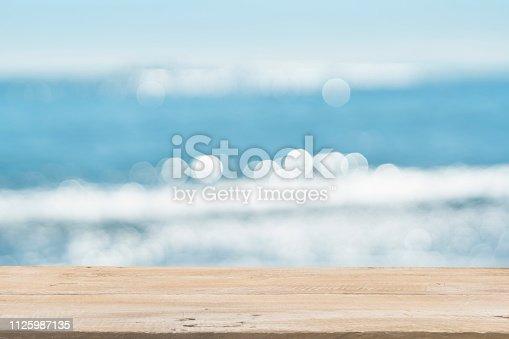 1125987088istockphoto Empty Wooden Planks with Blur Beach on Background 1125987135