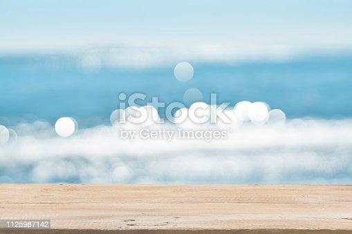 1125987088istockphoto Empty Wooden Planks with Blur Beach on Background 1125987142