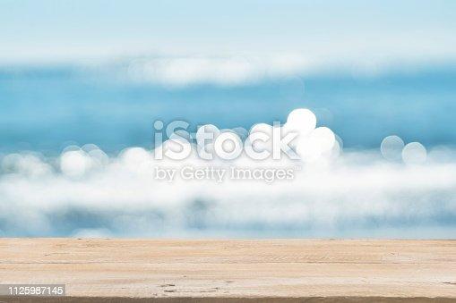 1125987088istockphoto Empty Wooden Planks with Blur Beach on Background 1125987145