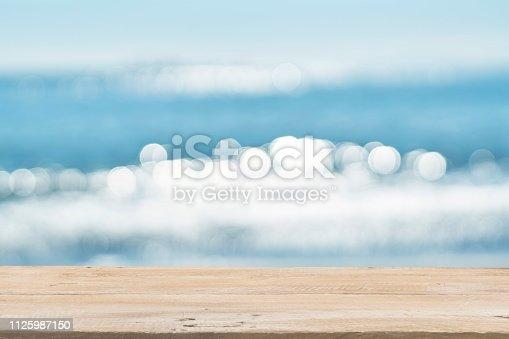 1125987088istockphoto Empty Wooden Planks with Blur Beach on Background 1125987150