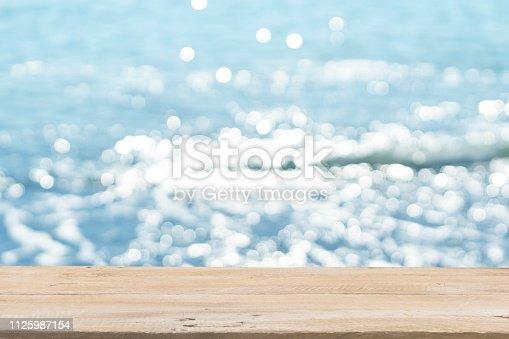 1125987088istockphoto Empty Wooden Planks with Blur Beach on Background 1125987154