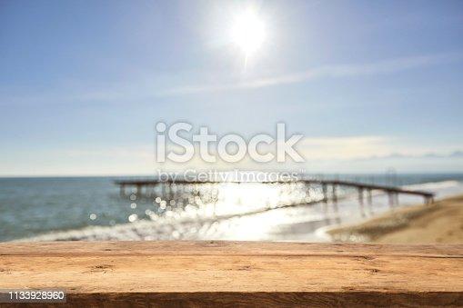 1125987088istockphoto Empty Wooden Planks with Blur Beach on Background 1133928960