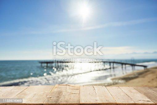 1125987088istockphoto Empty Wooden Planks with Blur Beach on Background 1133928969