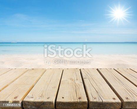 Empty wooden platform beside sandy beach in the sun