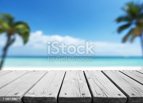 641254964 istock photo Empty wooden platform with blurred tropical beach background 1155138671