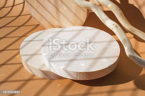 istock Empty wooden podiums on beige background. Round pedestal for product advert in rainbow flare light mockup 1315254852