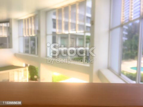 662984906 istock photo Empty wooden railing with blurred window and light background. 1153888638