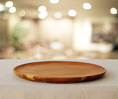 Empty wooden round tray over blurred cafe with bokeh light background, food and product display montage