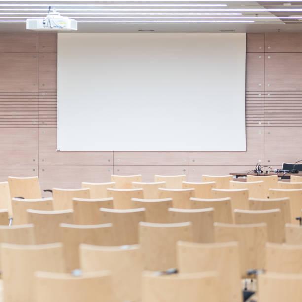 Leere Holzsitze in einem kinderkandären Hörsaal. – Foto