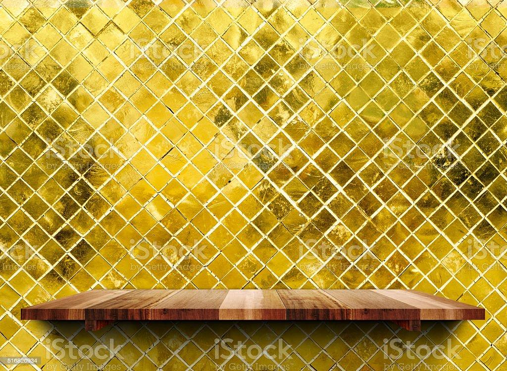 Shelfs in legno vuota sulla parete di mosaico piastrelle lucida oro