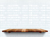 Empty wooden shelfs on white glossy tile wall,