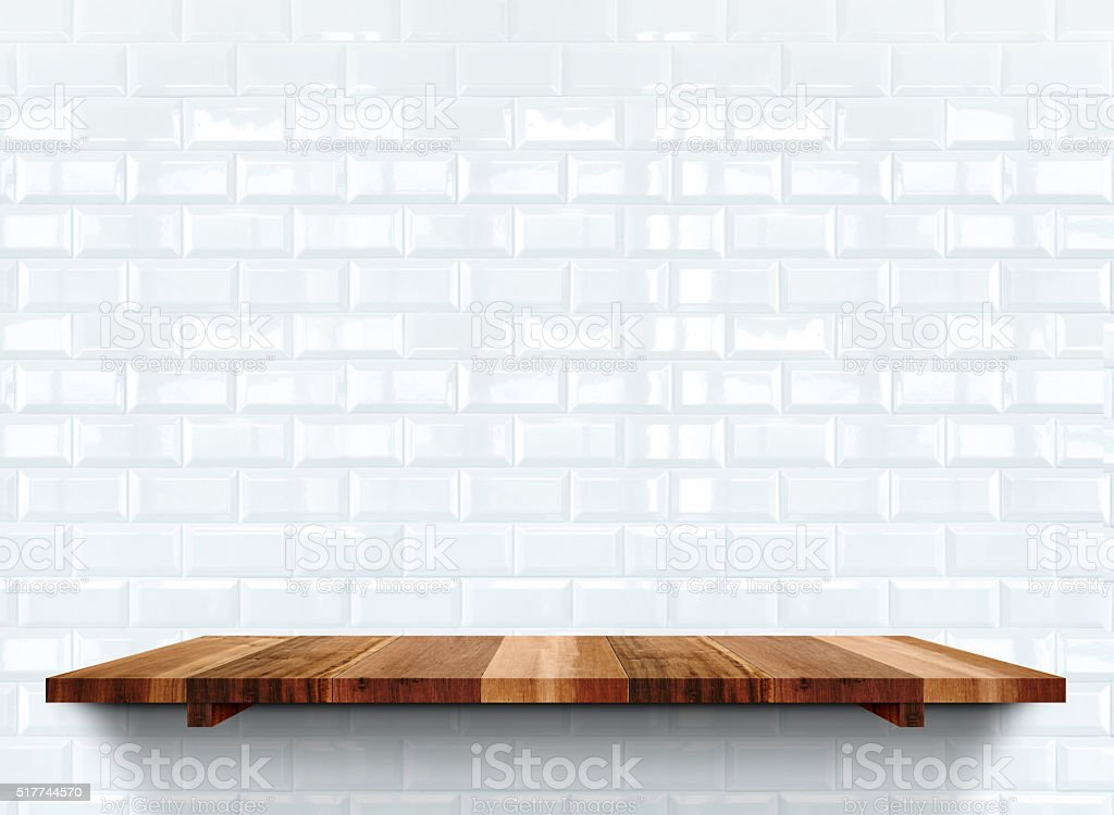 Empty wooden shelfs on white glossy tile wall, stock photo
