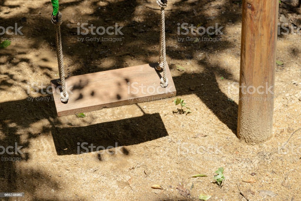 empty wooden swing with sunlight in playground zbiór zdjęć royalty-free