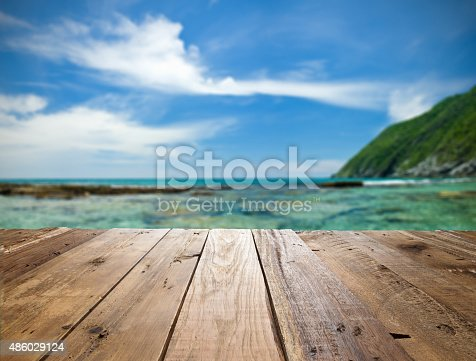 Empty wooden table against defocused tropical beach with turquoise water and deep blue sky, spotlight effect in the center of the frame. Ideal for product display on top of the table