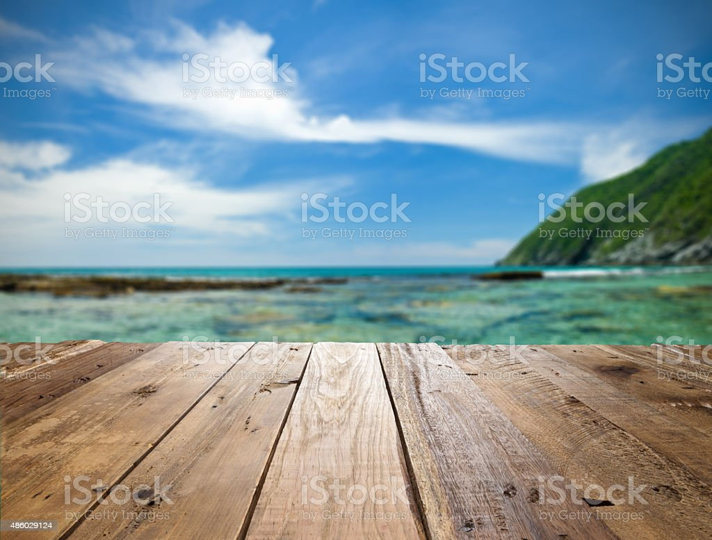 Empty wooden table against defocused tropical beach stock photo