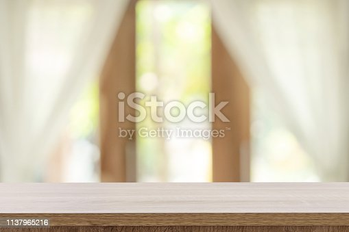 885452818istockphoto Empty wooden table and blur window background with copy space, display montage for product. 1137965216