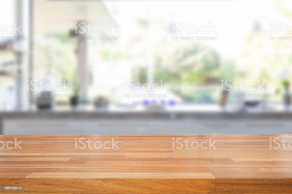 Pusty drewnianym stole w kuchni i niewyraźne tło – zdjęcie