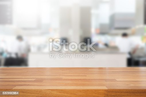 istock Empty wooden table and blurred kitchen background 530990964