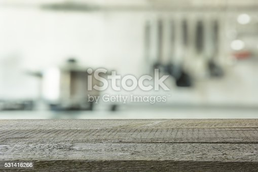 607472174istockphoto Empty wooden table and blurred kitchen background. 531416266