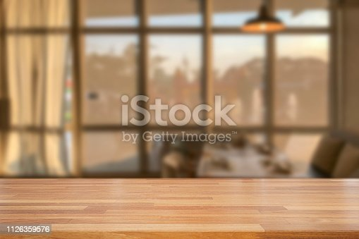 istock Empty wooden table and blurred modern  kitchen coffee cafe background with windows, restaurants. Ready for product montage, bokeh , warm light 1126359576
