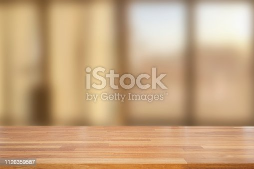istock Empty wooden table and blurred modern  kitchen coffee cafe background with windows, restaurants. Ready for product montage, bokeh , warm light 1126359587