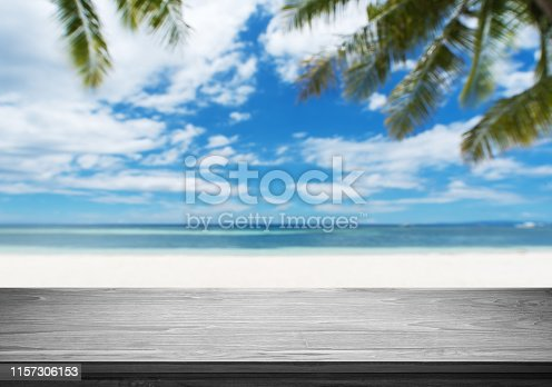 641254964 istock photo Empty wooden table and blurred tropical beach background 1157306153