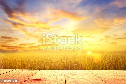 empty wooden table and field at sunrise