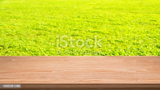 989111446istockphoto Empty Wooden Table And Green Field Abstract Background 1053261260