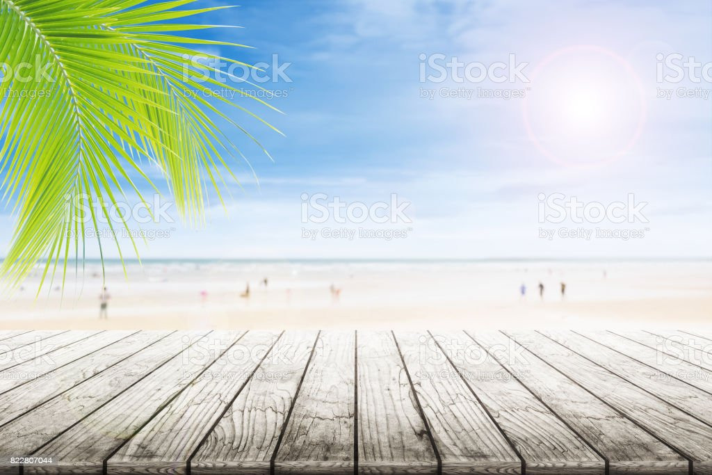 Empty wooden table and palm leafs with party on beach background blurred. stock photo