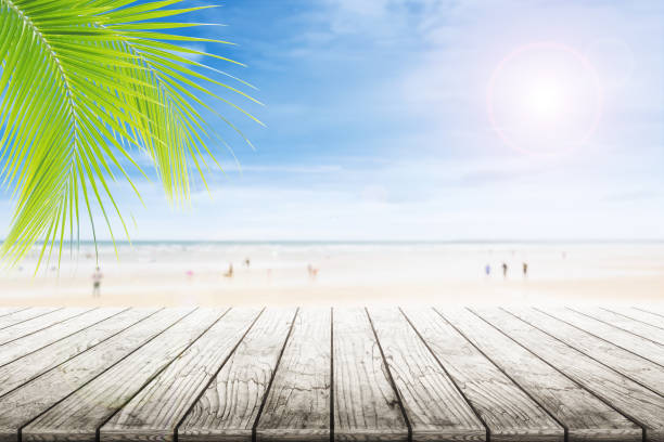 Empty wooden table and palm leafs with party on beach background blurred. - foto stock