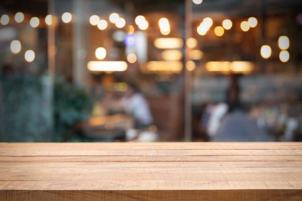 lege houten tafel en foto wazig restaurant of café. - restaurant table stockfoto's en -beelden