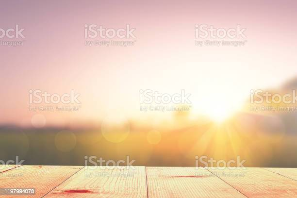 Photo of empty wooden table and sunrise nature background