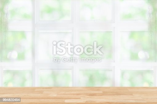 1002094650istockphoto Empty wooden table and window room interior decoration background, product montage display,can be used for display or montage your products.Mock up for display of product. 994820454