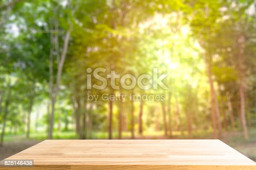 989111446istockphoto Empty Wooden table for display product and blurry forest in background 825146438