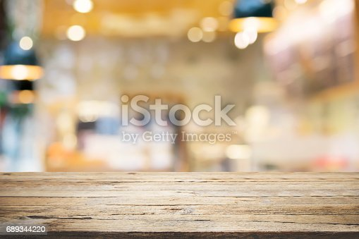 istock Empty wooden table for present product on coffee shop or soft drink bar blur background with bokeh image 689344220