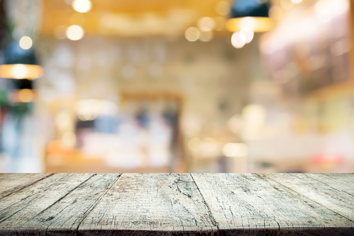 istock Empty wooden table for present product on coffee shop or soft drink bar blur background with bokeh image 689344224