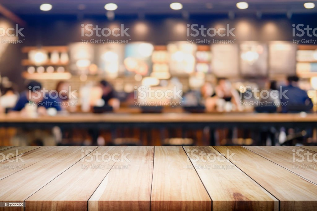 Empty wooden table for present product on coffee shop or soft drink bar blur background with bokeh image. stock photo