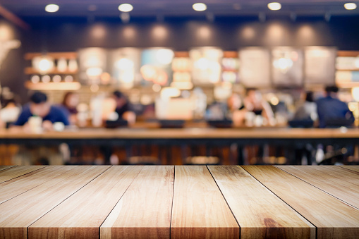 Empty Wooden Table For Present Product On Coffee Shop Or Soft Drink Bar Blur Background With Bokeh Image Stock Photo - Download Image Now