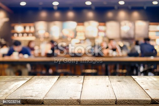 istock Empty wooden table for present product on coffee shop or soft drink bar blur background with bokeh image. 847023214