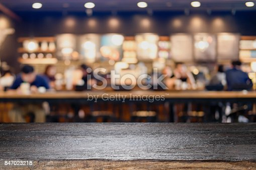 istock Empty wooden table for present product on coffee shop or soft drink bar blur background with bokeh image. 847023218