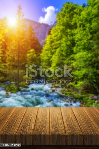 989111446istockphoto Empty wooden table for product placement or montage with focus to table top in the foregrounEmpty wooden table for product placement or montage with focus to table top in the foreground. Mock up for display of product. Beautiful background with forest, wa 1137051238